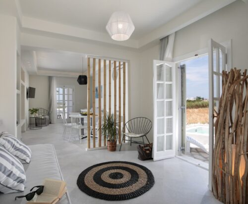Sofa near the window, modern chairs and dining area at Clio Villa with outdoor jacuzzi in Naxos.